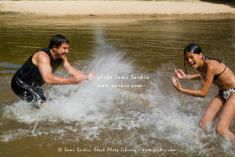 Man splashing a young girl in the Eyre river, Aquitaine, France.