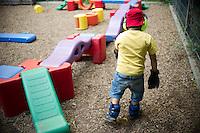 """Berlin, Ein Kind mit Gewichten, Handschuhen und Kopfhörern geht am Mittwoch (12.06.13) in der Kindertagesstätte (Kita) Reuterstraße bei der frühkindlichen Bildungsinitiative """"Tag der kleinen Forscher"""" der Stiftung """"Haus der kleinen Forscher"""" durch einen Parkour. Das Experiment soll verdeutlichen, wie es sich anfühlt alt zu sein. Foto: Steffi Loos/CommonLens"""