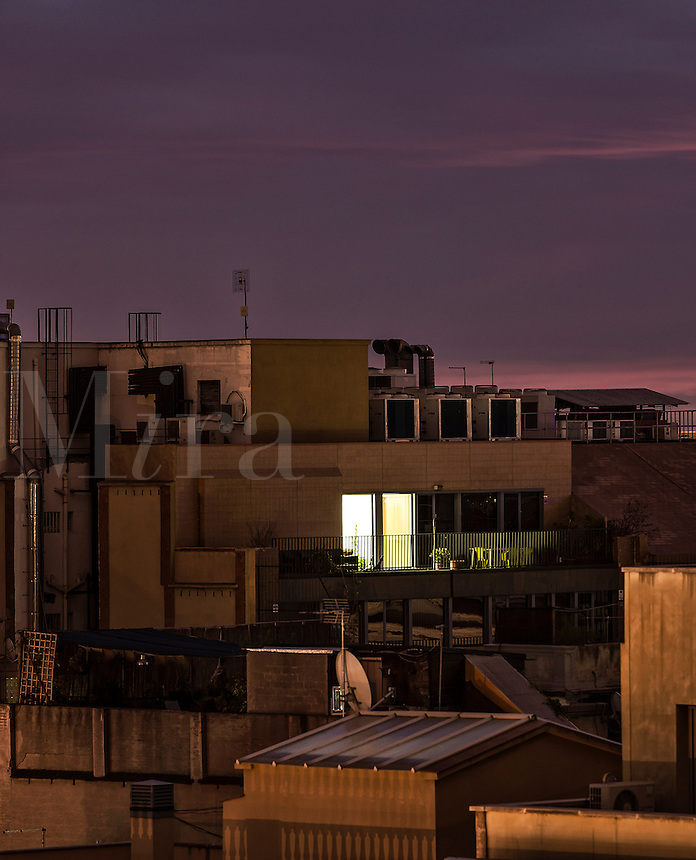 A single apartment light shines through the dark facade of a downtown building.
