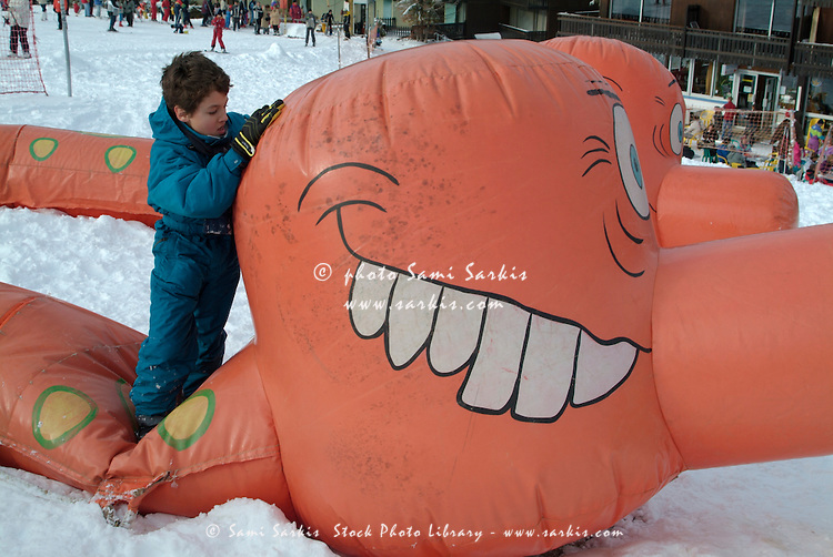 Nine year old boy playing on a giant inflatable toy at a ski resort in the French Alps, France.