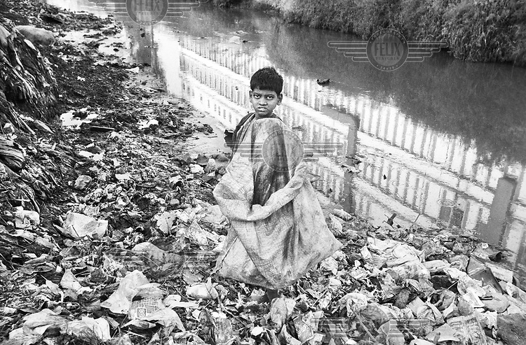A boy scavenging for plastic bottles and other reusable items in an open sewer in a slum area.