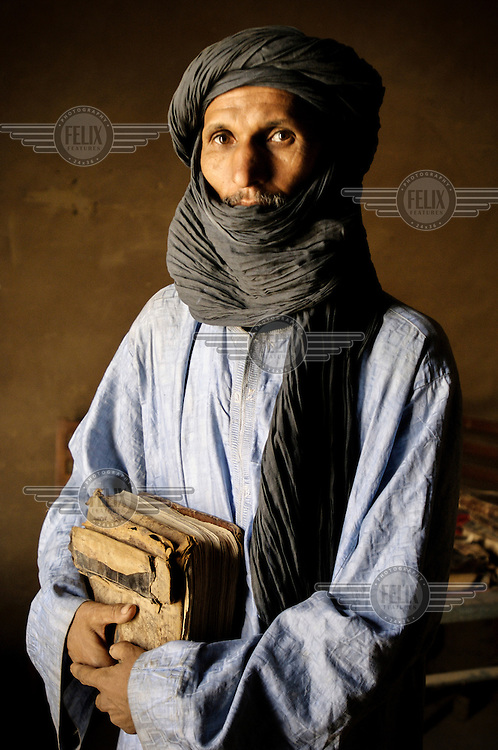 A portrait of a man holding recovered manuscripts at a library in Timbuktu. /Felix Features