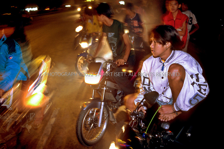 June, 2001--Bangkok,   Thailand..The 'flies, illegal bike racers in Bangkok, Thailand. The 2-stroke engines fill the air with noxious fumes that sting the eyes and choke the lungs...The Thais call them maleang wan, or ?flies?. You see the illegal motorcycle racers every day on the streets of Bangkok. Tearing through the traffic, weaving in and out of the city?s permanently stalled traffic, you can hear the distinctive high pitch screams of their modified 75 & 125cc engines. By day they are dispatch riders, delivery boys, motorcycle taxi drivers or just bored teenagers out cruising the streets but at night they are Bangkok?s infamous racers?daredevils whose exploits and accidents have become regular gristle for the pages of Thai newspapers...All photographs ©2007 Stuart Isett.All rights reserved.This image may not be reproduced without expressed written permission from Stuart Isett.