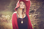A beautiful  young woman with blonde hair wearing a red hat standing in the nature