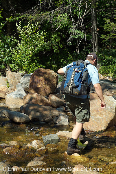 A hiker crosses one of the many river crossings along the Rocky Branch Trail in the White Mountains of New Hampshire during the summer months.