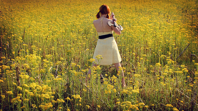 A young woman wearing a yellow dress standing in a field of yellow flowers holding an axe