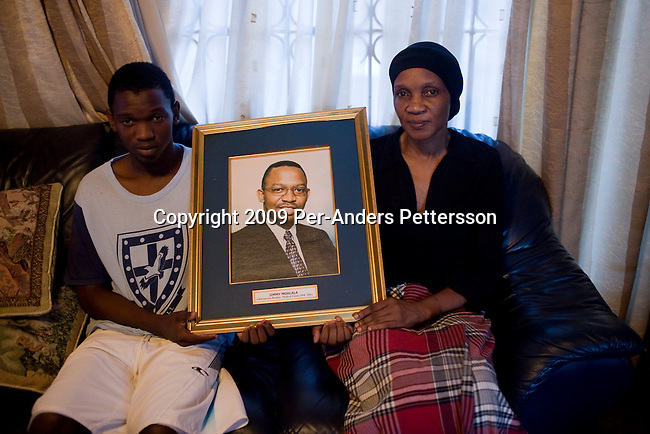 NELSPRUIT, SOUTH AFRICA FEBRUARY 18: Tshipiso Mohalala, age 19, and his mother Bonny Mahalala holds a portrait of his killed father and husband on February 18, 2009 in Nelspruit, South Africa. Bonny?s husband, Jimmy Mohalala was shot and killed a few months ago by unknown attackers. Tshipiso was wounded in the leg but managed to hide in the family house. The father had uncovered corruption with the building of the new stadium for the 2010 Soccer World Cup. Nelspruit is one of the host cities for the event. The project has been affected by strikes and many delays. (Photo by Per-Anders Pettersson/Getty Images).