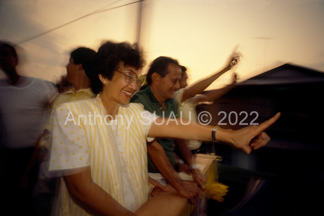 Manila, Philippines<br /> February 1986<br /> <br /> Corazon Aquino campaigning for President of the Phippines.<br /> <br /> The People Power Revolution was a mostly nonviolent mass demonstration in the Philippines. <br /> <br /> In November 1985, President Ferdinand Marcos announced snap presidential elections be held in 1996, one year ahead of schedule. The opposition candidate was Corazon Aquino and Marcos himself ran for re-election. The elections were held on February 7. The electoral exercise was marred by widespread violence and tampering of election results. The official election canvasser, the Commission on Elections (COMELEC), declared Marcos the victor. The National Movement for Free Elections (NAMFREL), an accredited poll watcher, had Aquino as the winner. Due to the reports of alleged fraud, the Catholic Bishops Conference of the Philippines (CBCP) issued a statement condemning the elections. The United States Senate passed a resolution stating the same. <br /> <br /> Four days of action with millions of Filipinos taking to the streets in Manila led to the downfall of the authoritarian regime of President Marcos. The Marcos family fled the country and was transported by American helicopters. Corazon Aquino was installed as the president of the Republic.