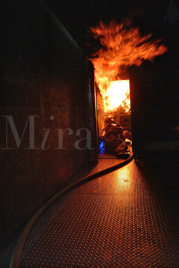 Firefighters attack a kitchen fire inside the fire training burn trailer during training with the Occidental Volunteer Fire Department