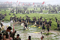 Chinese People's Liberation Army soldiers work to remove blue green algae off of a beach in Qingdao, China. The massive algal bloom is due to the pollution that has been swept down from the mainland in the recent heavy rain in the bobai sea. Qingdao is where the Olympic sailing events will be held and it will be race against time to clear the sea area in time for the Olympics which start in 40 days..03 July 2008.
