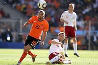 Wesley Sneijder of Holland gets away from Martin Jorgensen of Denmark