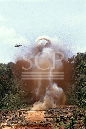 Roraima, Brazil. Military helicopters flying over an illegal garimpeiro gold prospector airstrip as it is exploded.