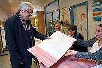 Bürgermeister Heinz-Peter Becker (SPD) bekommt die Stimmzettel von Christina Kursim in der KiTa Parkstraße im Wahlbezirk 110 in Mörfelden-Walldorf