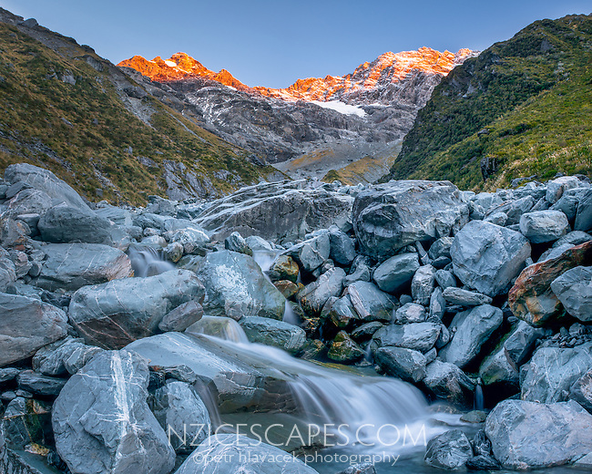Unnamed creek and sunset over Southern Alps near Ice Lake, Westland National Park, West Coast, New Zealand