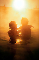 Backlit couple embracing in hot springs
