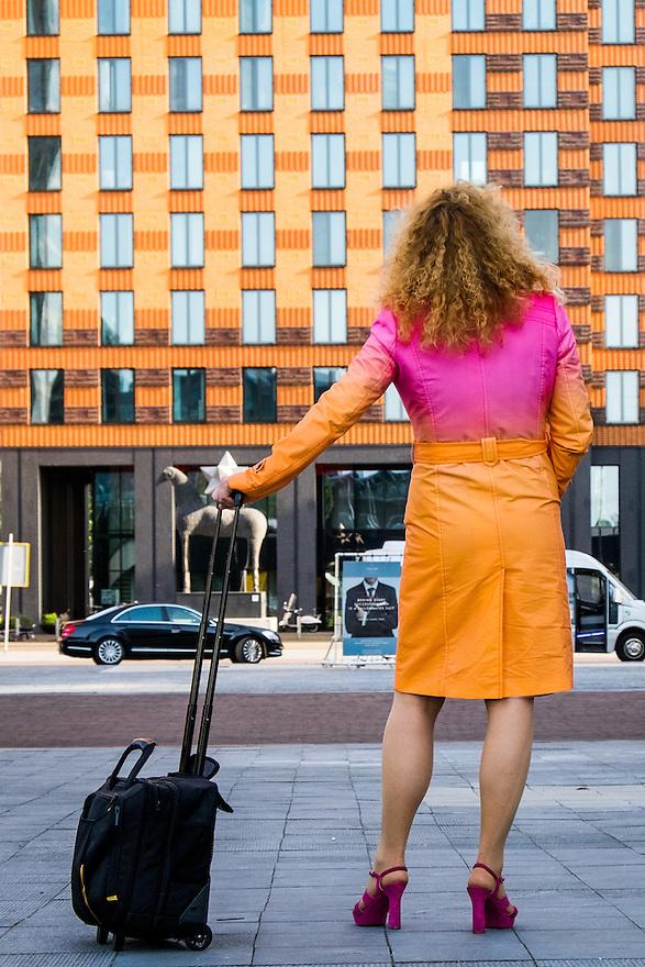 Nederland, Amsterdam, 16 juli 2015<br /> Amsterdam Zuidas. Vrouw in mooi gekleurde jas wacht op een kennis. <br /> <br /> Foto: Michiel Wijnbergh