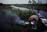 A camper checks the fire as he cooks for the evening meal on a three day wilderness canoe trip through the Okefenokee Swamp. <br /> <br /> Okefenokee means &quot;Land of the Trembling Earth&quot; in a Native American language. The term refers to the natural processes as peat bubbles up from the bottom of the swamp, vegetation attaches itself, and plants begin growing to form little islands. The effect of walking on this unstable land as been described as being able to dance with a tree of similar weight.