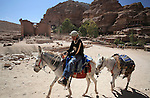 A Bedouin boy and his donkeys in the ancient city of Petra in Jordan. Petra is the most visited tourist attraction in Jordan, a symbol of the country for its historical and archaeological importance. It has been a UNESCO World Heritage Site since 1985. The Bedouin families that have been living for centuries in the caves of Petra, agreed to move out into a small village, built near the site of Petra. Most of them earn their living from tourism which seems to be the only option available, especially for the younger generations.