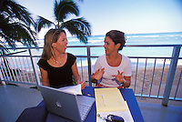Two women working with papers and computer on veranda in a tropical Hawaiian setting