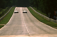 Two cars race away from the exit of Mulsanne Corner, late afternoon, during the 1985 24 Hours of Le Mans auto race.