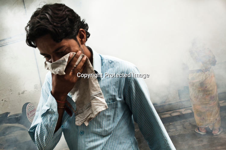 Residents cover their face while a civic worker fumigates the streets to prevent the spread of malaria and dengue fever in New Delhi, India.