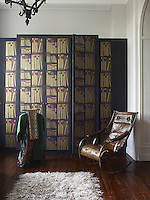 The cupboard in the dressing room is covered in Fornasetti wallpaper and the iron and leather rocking chair is antique