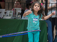 NWA Democrat-Gazette/ANTHONY REYES &bull; @NWATONYR<br /> Sofia Ramirez, 5, tries a hula hoop Tuesday, Aug. 18, 2015 during a block party and ribbon cutting for the Immigrant Resource Center in Springdale. The Center is the first of five planned for the state. It is a cooperation between Arkansas United Community Coalition and Catholic Charities Immigration Services of Northwest Arkansas and will provide area immigrants with immigration navigation services, leadership development opportunities, and civic integration support. The event introduced the public to the services provided by the center and several other organizations were on hand to distribute information about their organizations.