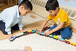 Education preschool 3 year olds two boys playing together with wooden train set