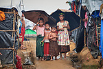 Rohingya refugee children share umbrellas as they walk though the sprawling Kutupalong Refugee Camp near Cox's Bazar, Bangladesh. More than 600,000 Rohingya refugees have fled government-sanctioned violence in Myanmar for safety in this and other camps in Bangladesh.