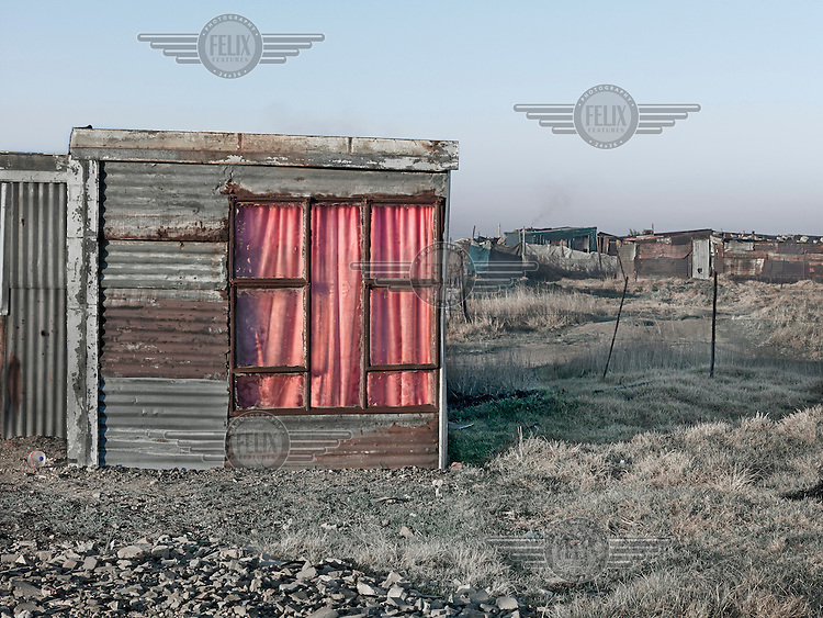 A small corrugated iron shacks. Graeme Williams' pictures of the environments occupied by some of South Africa's poorest people focus on the interiors and exteriors of people's homes, accentuating the minutiae of the occupants' day-to-day dwelling places. The bright colours captured in these photographs are suggestive of resilience, hope and a sense of humanity that survives in these poverty-stricken communities...