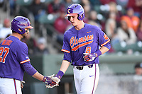Shortstop Logan Davidson (8) of the Clemson Tigers is congratulated by Chris Williams after scoring a run in the Reedy River Rivalry game against the South Carolina Gamecocks on Saturday, March 3, 2018, at Fluor Field at the West End in Greenville, South Carolina. Clemson won, 5-1. (Tom Priddy/Four Seam Images)
