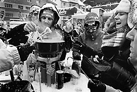 Switzerland. Canton Bern. Wengen. A group of friends from the Gruyère area (Fribourg) eat a traditional cheese fondue outside during the FIS Ski World Cup Lauberhorn. Fondue is a Swiss dish of melted cheese served in a communal pot (caquelon or fondue pot) over a portable stove (réchaud) heated with a candle or spirit lamp, and eaten by dipping bread into the cheese using long-stemmed forks. It was promoted as a Swiss national dish by the Swiss Cheese Union (Schweizerische Käseunion) in the 1930. Wengen is a mountain village in the Bernese Oberland of central Switzerland. Located in the canton of Bern at an elevation of 1,274 m above sea level, it is part of the Jungfrauregion. 14.01.17 © 2017 Didier Ruef