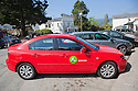 A red car by the car sharing company Zip Car in a parking lot in Bolinas. Customers pay by the hour or day to use the car which have dedicated parking spaces in cities. Bolinas, California, USA