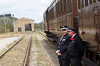 Due ferrovieri davanti a un treno d'epoca degli anni Venti in occasione della presentazione degli itinerari storici proposti dal Ministero dei Beni Culturali e del Turismo e dalla Fondazione FS Italiane, sui binari della stazione di Torrenieri-Montalcino, lungo il tracciato dell'antica ferrovia della Val d'Orcia, 11 aprile 2015.<br /> Two rail workers in front of a vintage train of the twenties traveling on the occasion of the presentation of the historical tours proposed by the Italian Culture and Tourism Minister and Fondazione FS Italiane (Italian Railways Foundation), at Torrenieri-Montalcino's railway station, along the Val d'Orcia, Tuscany, 11 April 2015.<br /> UPDATE IMAGES PRESS/Riccardo De Luca