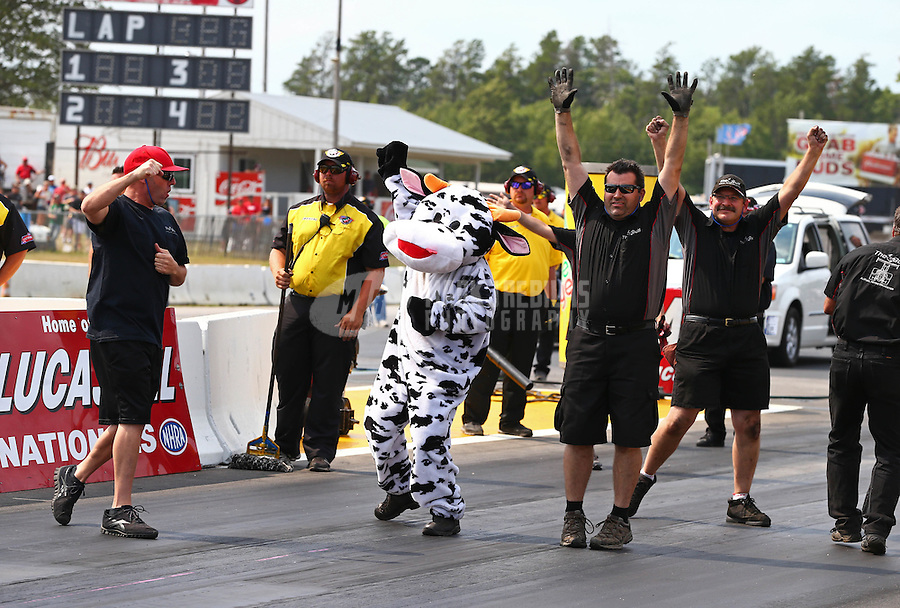 Aug. 18, 2013; Brainerd, MN, USA: Crew member for NHRA top alcohol dragster driver Gord Gingles dressed as a cow celebrates during the Lucas Oil Nationals at Brainerd International Raceway. Mandatory Credit: Mark J. Rebilas-