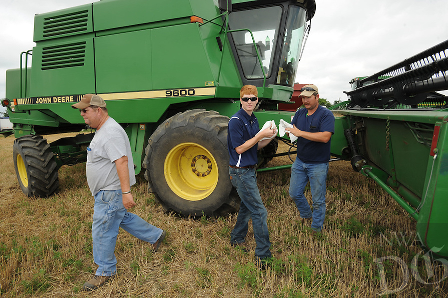 STAFF PHOTO ANDY SHUPE - Allen Moore, right, his brother, Curtis, center, and father, Ralph, remove the head from their tractor while combining wheat Friday, June 27, 2014, at a farm north of Prairie Grove.