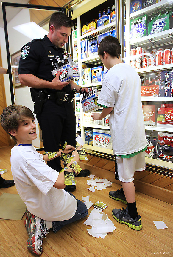 Members of the Granite State Youth Alliance, Deven Carroll, 12, of Exeter, left, and, Tanner Spinney, 12, of Deerfield, right, work with School Resource officer Mike Oliveira, labeling beer at a local store in Stratham, N.H., Thursday, May 17, 2012. (Portsmouth Herald Photo Cheryl Senter)
