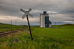 Washington, Eastern, Palouse Region, Pullman. A railroad crossing sign marks the tracks near a grain elevator in late spring.