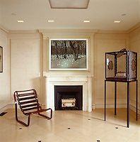 In this contemporary Manhattan town house artworks are displayed alongside a designer chair and a period fireplace in the entrance hall