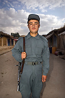 An Afghan National policeman stands with a rifle slung over his shoulder.