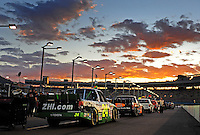 Nov. 13, 2009; Avondale, AZ, USA; NASCAR Camping World Truck Series trucks sit on pit road as the sun sets prior to the Lucas Oil 150 at Phoenix International Raceway. Mandatory Credit: Mark J. Rebilas-