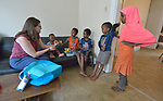 Christine Baer, a congregational resource developer with Church World Service in Lancaster, Pennsylvania, delivers a backpack full of books and art supplies to children of a recently arrived refugee family from Eritrea. Church World Service resettles refugees in Pennsylvania and other locations in the United States. <br /> <br /> Photo by Paul Jeffrey for Church World Service.