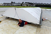 Second One Day International - Scotland V Ireland at Mannofield, Aberdeen - Mannofield Head Groundsman Kenny McCurdie appears to stretch himself into checking for water damage under the covers at the Aberdeenshire CC ground after the 2nd ODI between Scotland and Ireland was abandoned because of heavy rain - Picture by Donald MacLeod 23.08.09