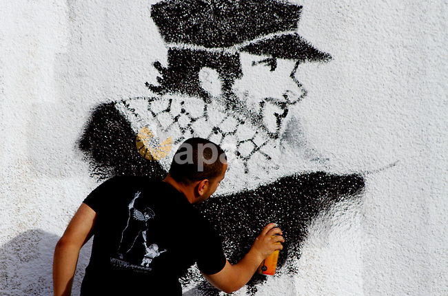 A Palestinian artist puts the final touches on a black and white mural painting dedicated to late Italian activist Vittorio Arrigoni in Gaza City on April 14, 2012, as Gazans marked the first anniversary of his murder in the northern Gaza Strip after being kidnapped by a fringe, radical Salafist group. Arrigoni, a 36-year-old member of the International Solidarity Movement (ISM), was found hanged last year in an abandoned house north of Gaza City after a radical Islamist group had posted a video of him online and threatened to kill him unless Hamas released an unspecified number of their members.. Photo by Ashraf Amra