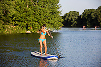 A fit athletic fitness women smiling on a perfect sunny summer day while stand up paddle boarding SUP on Lady Bird Lake in Austin, Texas.