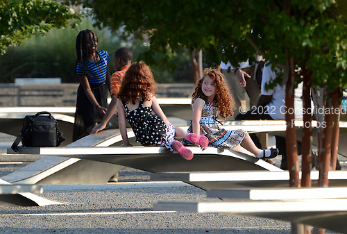 Children rest on the benches of the Pentagon Memorial at the Pentagon in Washington, DC on September 11, 2013.  United States President Barack Obama will commemorate the 12th anniversary of the 9/11 terrorist attacks that killed nearly 3,000 people in New York, Washington and Shanksville, Pennsylvania.  There are 184 benches in the Pentagon Memorial representing the 184 people who died at the Pentagon on September 11, 2001.   <br /> Credit: Pat Benic / Pool via CNP