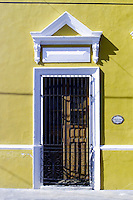 White doorway against yellow-ochre walls on house in Merida, Mexico.