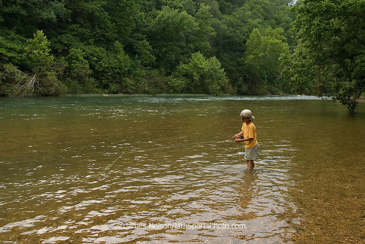 A nine-year-old boy fly fishes for bluegill on the James River, Missouri.