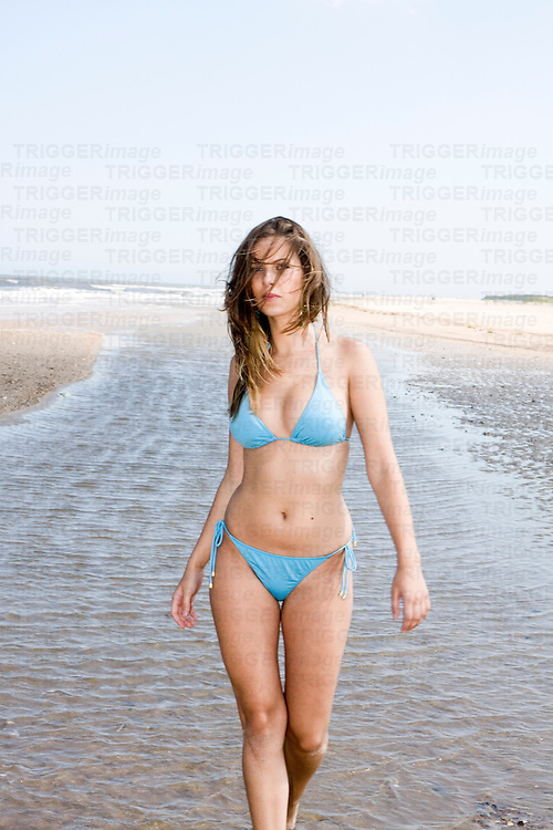A young girl in a bikini walking along the edge of the sea in Holme-Next-The-Sea, a seaside resort on the north Norfolk Coast.