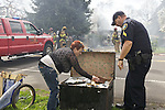 04/01/13-- Darlene Malone looks through a trunk-full of pictures and pther memoirs that firefighters from Tualatin Valley Fire & Rescue saved in Tigard. According to witnesses the fire started around 1 PM. .Photo by JaIme Valdez